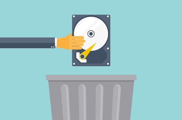 Hånd holder en harddisk over en søppelkasse.