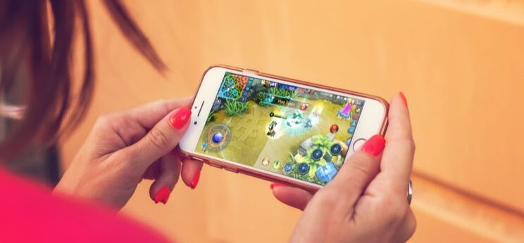 Någon som spelar Mobile Legends: Bang Bang på en mobiltelefon.