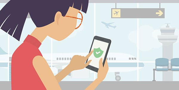 Een vrouw op een vliegveld die haar telefoon beschermt met een VPN.